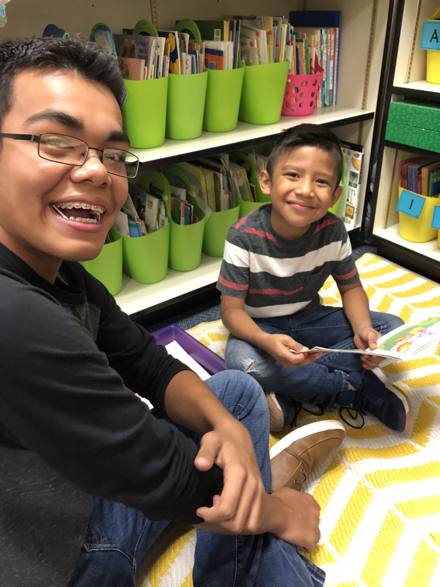 High school student reading with 1st grade student